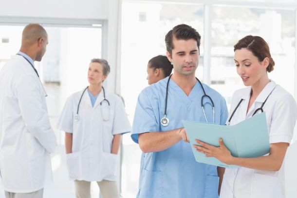 Nurse talking to doctor with doctors in background