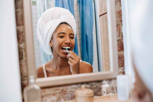 black woman cleaning teeth with flosser