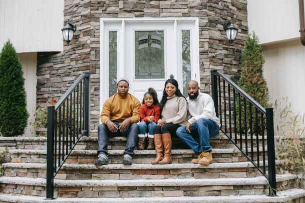 smiling black family on house stairs in daylight