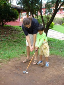 Teaching young boy golf swing