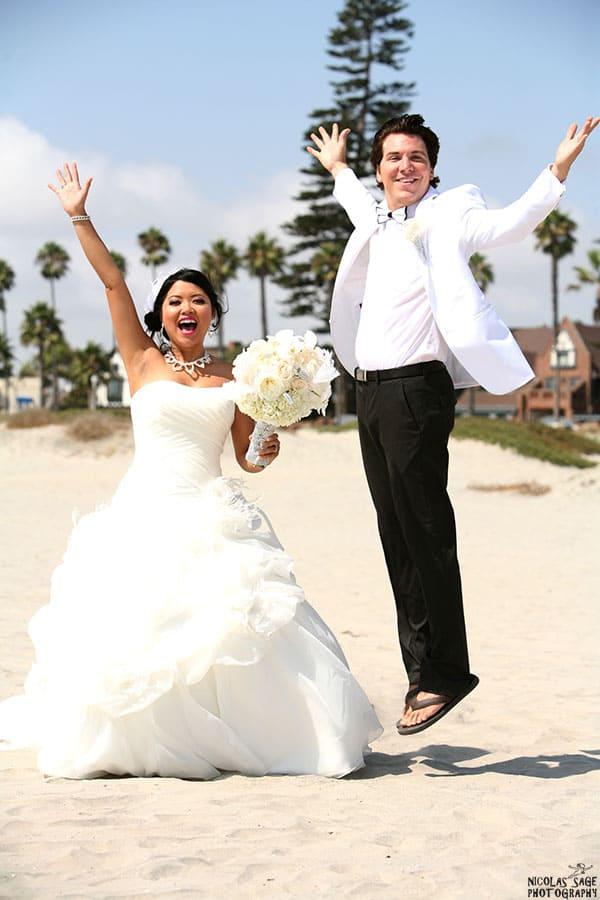 bride and groom jumping at their Coronado beach wedding in San Diego