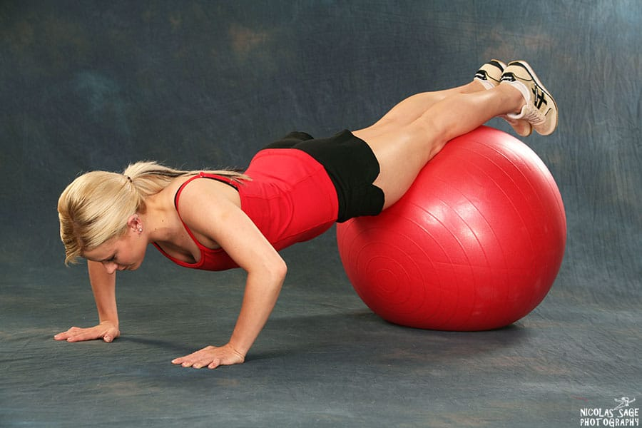 blonde fitness woman doing push ups with exercise ball