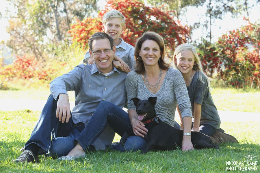outdoor family portrait of family with a black dog