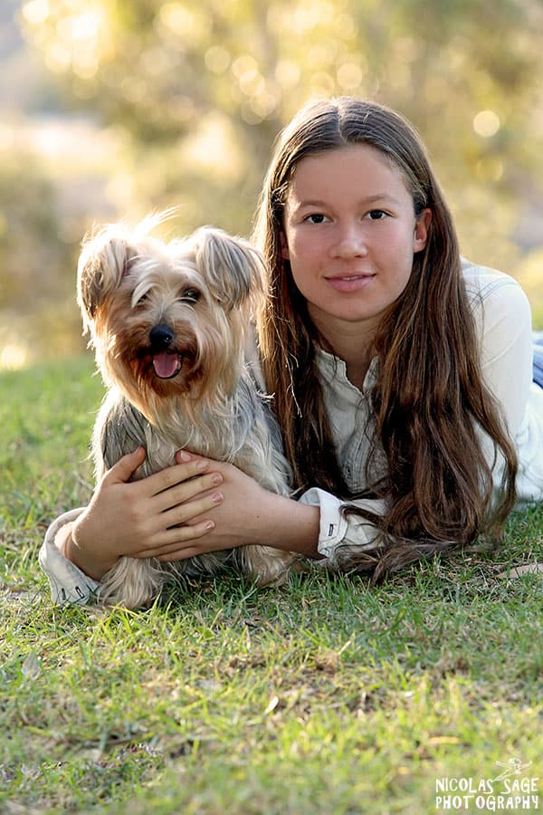 teen girl at park posing with her dog