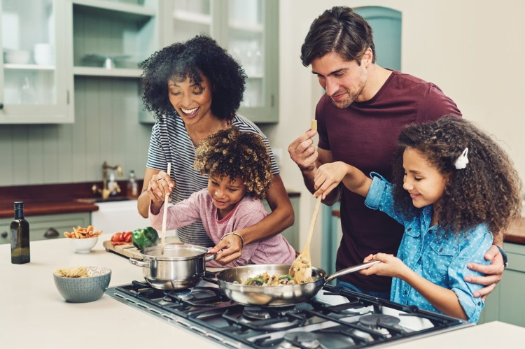Shot of a family of four cooking together in their kitchen at home
