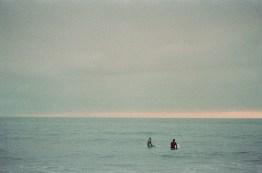 surf couple engagement photos on beach film crystal cove