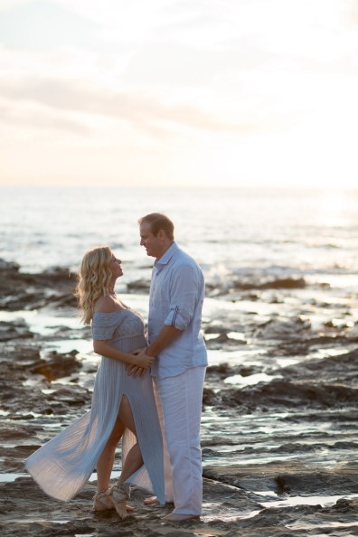 orange county maternity photographer nicole caldwell crystal cove beach couple holding hands on rocks