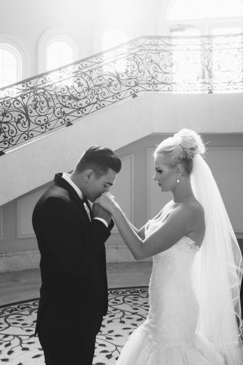 bride and groom starits groom kissing brides hand Monarch beach resort wedding photographer nicole caldwell