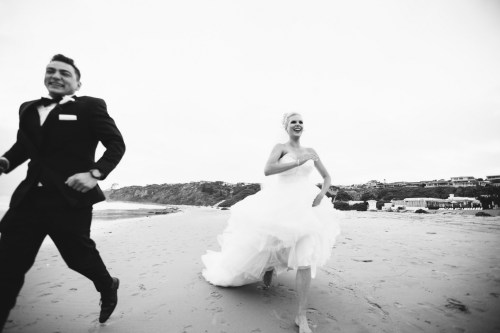 bride and groom running on beach Monarch beach resort wedding photographer nicole caldwell