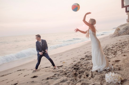 bride and groom play with beach ball wedding photos surf and sand resort laguna beach