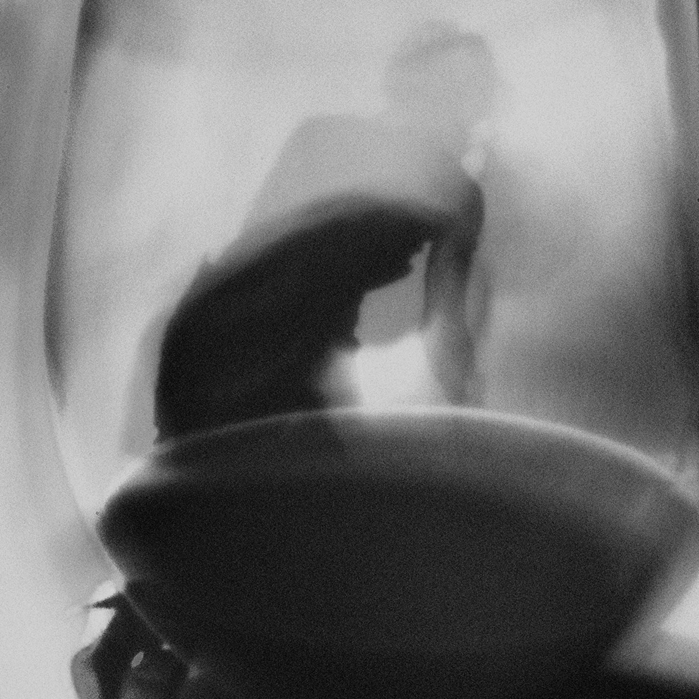 Black and white photo of woman on high heels on the floor seen through glass filled with wine