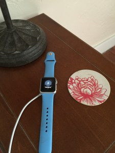 Apple Watch charging on the bedside table.