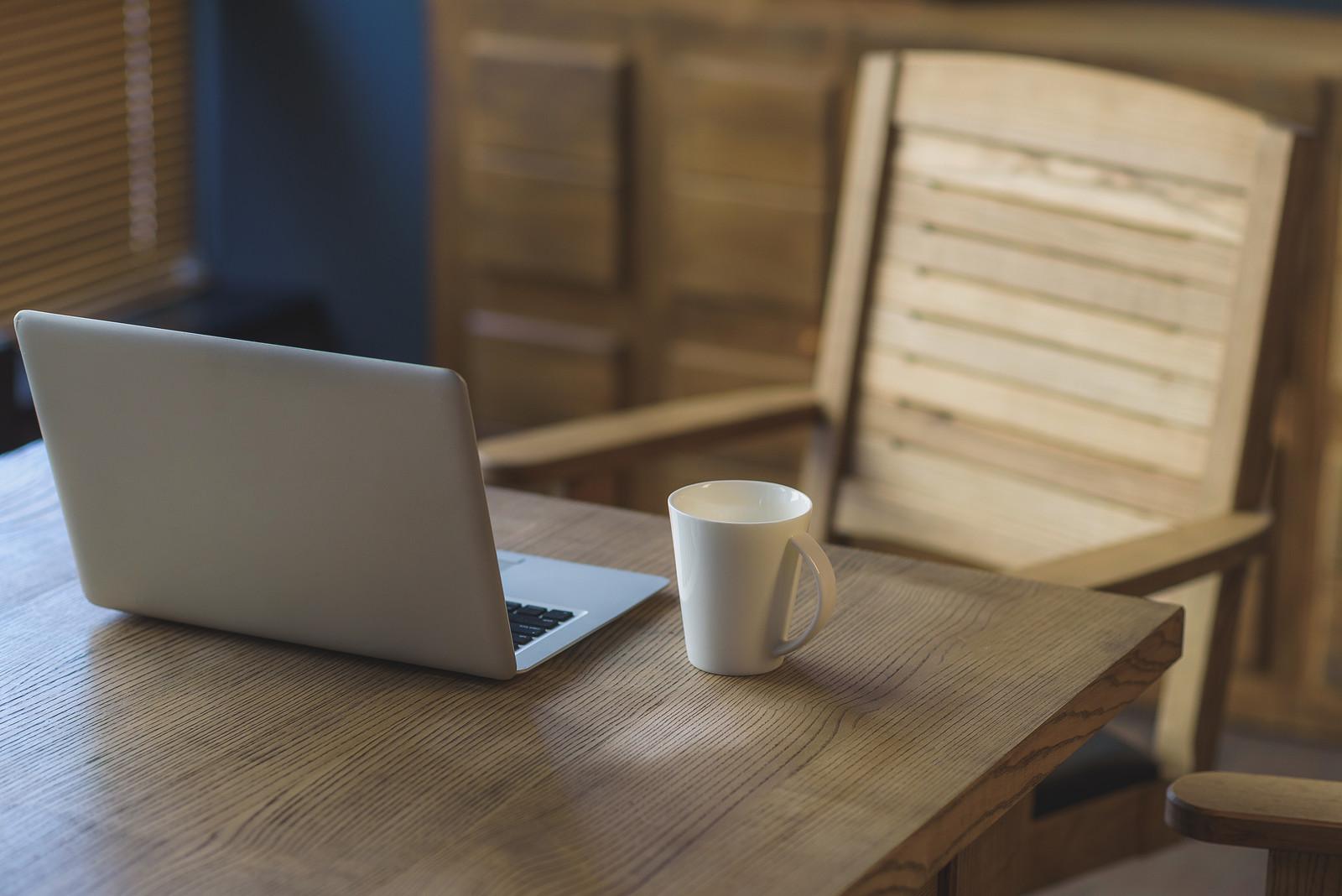 Laptop and mug of tea on a table.