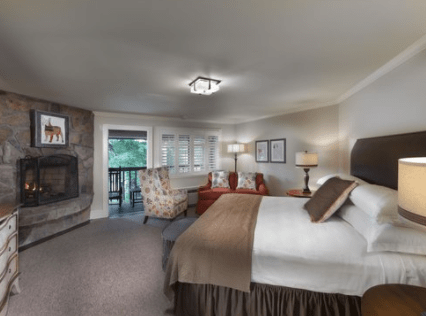 Large King room with fireplace and balcony is updated hotel with mountain chic decor.