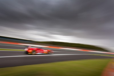 Burred image of car going fast against a grey cloudy sky