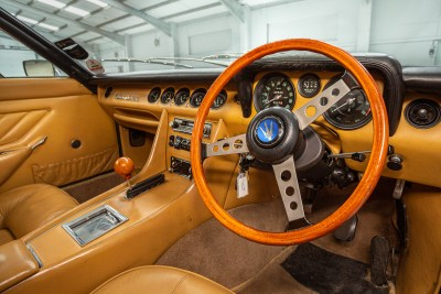 Light brown leather interior view of steering wheel and dashboard of a 1971 Maserati Indy America 4700
