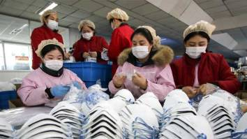 This photo taken on January 22, 2020 shows workers producing facemasks at a factory in Handan in China's northern Hebei province. STR / AFP