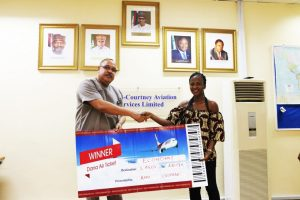 Chief Executive Officer of Bi-Courtney Aviation Services Limited (BASL), operator of the Murtala Muhammed Airport Terminal Two (MMA2), Lagos, Captain Jari Olubunmi Williams (left), presenting a free flight ticket to the first winner of MMA2 mobile application promo, Ms. Anuoluwapo Olopade, a lawyer, in Lagos recently. Tickets for the promo were supplied by Dana Air.
