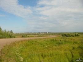 Дорога из посёлка к аэропорту и парому. Вдали за Енисеем (его сэтой точки не заметно) виднеется заброшенный Лесопильноперевалочный комбинат