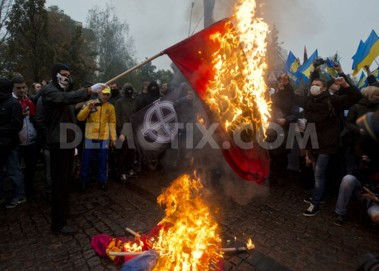October, 2013: Activists of Ukrainian nationalist parties burn take part in a rally marking the 71st anniversary of the Ukrainian Insurgent Army and the feast of the Protecting Veil of the Mother of God in central Kiev. In the background, the fascist Christian flag can be clearly seen.