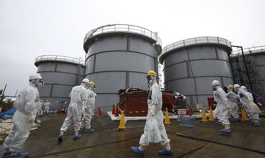 File-photo-of-members-of-the-media-and-TEPCO-employees-wearing-protective-suits-and-masks-walking-past-storage-tanks-in-Fukushima-prefecture_1397203590261921_v0_h