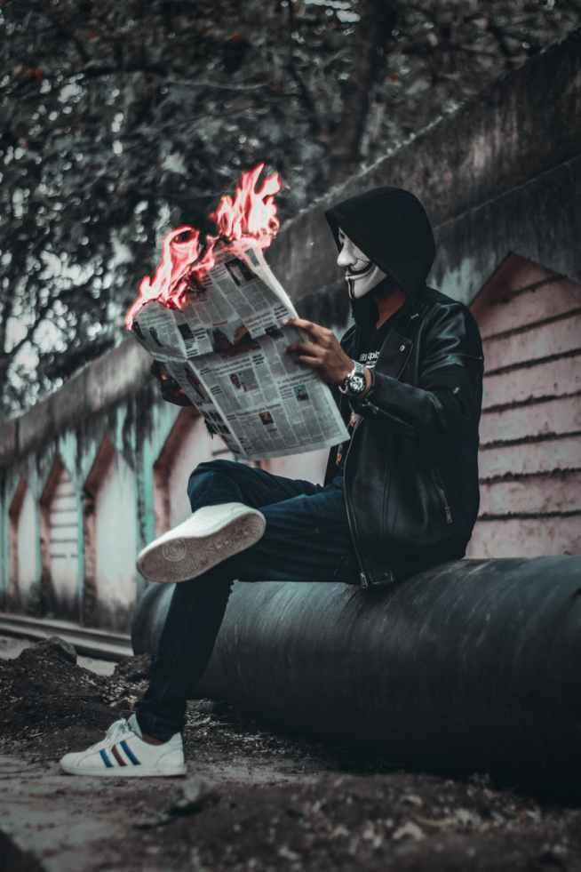 man wearing mask sitting down and holding newspaper with fire