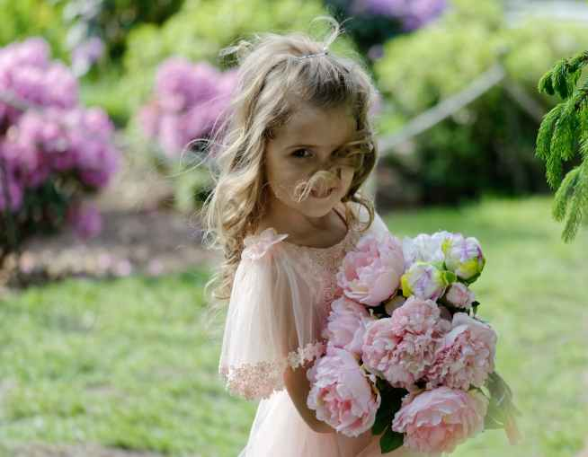 shallow focus photo of girl holding pink flowers