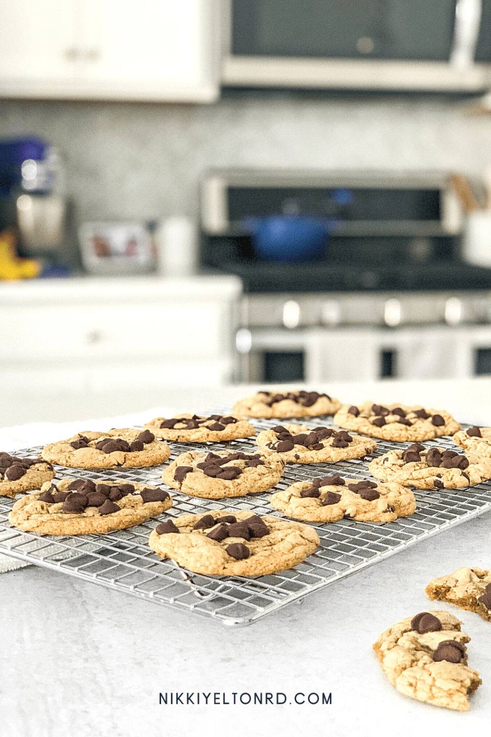 Warm grain-free chocolate chip cookies on a baking rack next to an oven