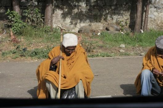 A beggar in the street, awaiting the end of mass.