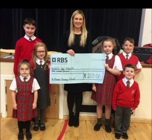 Emma collects the cheque from some of the pupils involved in the fundraising