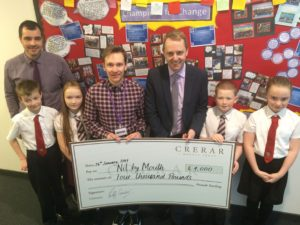 Staff from Crerar Hotels hand over the cheque to NbM Education Officer Jamie Lithgow and pupils from Cairns & St Cadoc's Primary Schools