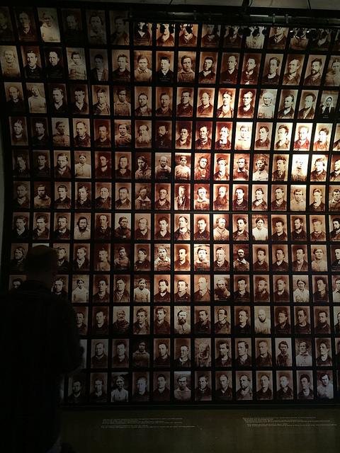 Udstillede billeder af tidligere tiders kriminelle - i skyggen min mand, der betragter dem.
