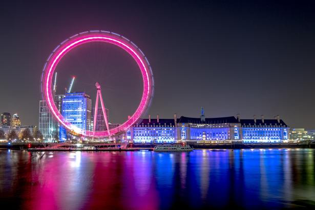 London Eye ferris wheel illuminated pink on an evening sky.