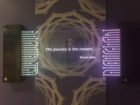 "Glass Sign that says ""The reward is in the journey"" - Steve Jobs"