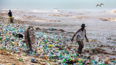Un uomo raccoglie materiale riciclabile nell'inquinatissima spiaggia di Korle Gono nel Ghana.