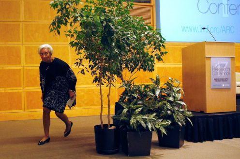 Christine Lagarde si acquatta dietro una pianta alla fine di un discorso pubblico.