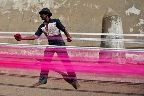 Un lavoratore tinge lo spago appeso al sole in India