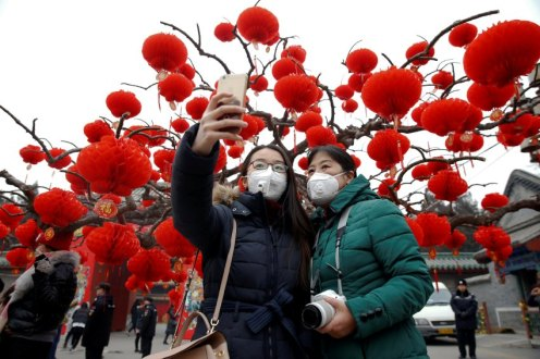 Visitors wearing face masks against pollution take pictures of themselves at the temple fair at Ditan Park (the Temple of Earth) as the Lunar New Year of the Rooster is celebrated in Beijing