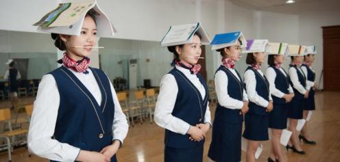 La vita delle hostess non è rose e fiori: in Cina ci si allena a mantenere l'equilibrio - e a sorridere.