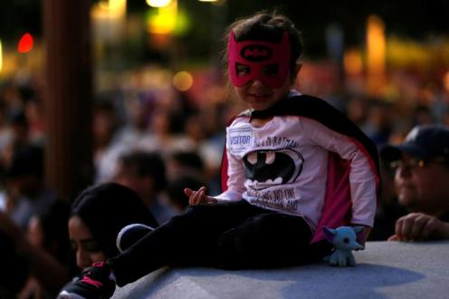 A young girl wears a costume before a bat-signal is projected on City Hall in honor of late actor Adam West in Los Angeles