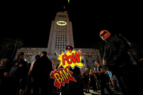 Enthusiasts Cleeland and de Felicis pose as a bat-signal is projected on City Hall in honor of late actor Adam West in Los Angeles