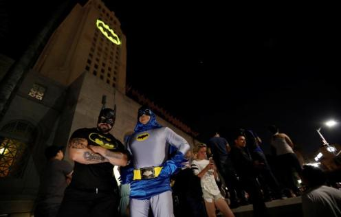 People wearing Batman costumes stand as a bat-signal is projected on City Hall in honor of late actor Adam West in Los Angeles