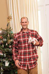 Farmer holding runt pig at Christmas