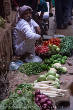 Vegetable vendor showing off his goods to sell on the floor