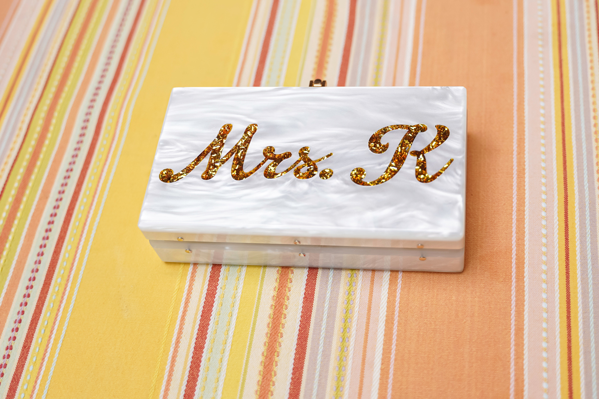 """Product photography of a pearlescent clutch with """"Mrs. K"""" etched into it."""