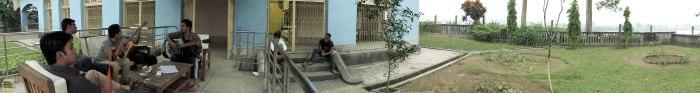 বারান্দায় গানের আসর, বাইরে বসা দুজন স্থানীয় শ্রোতা, বাংলো থেকে প্যানোরামা (ছবি: লেখক)