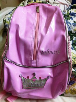 """The return gift - a backpack embossed with the snubnose's name and a little crown saying """"Princess"""""""