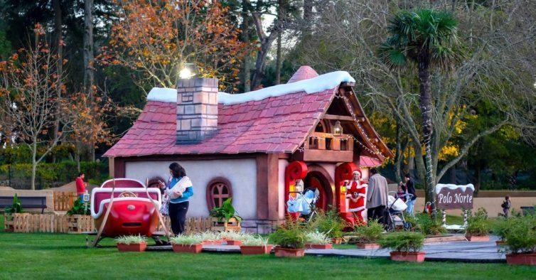 Pátio com a casa do Papai Noel, enfeitada com luzes de Natal. Uma duende recebe os convidados na porta da casa. trenó vermelho do Papai Noel ao lado da casa