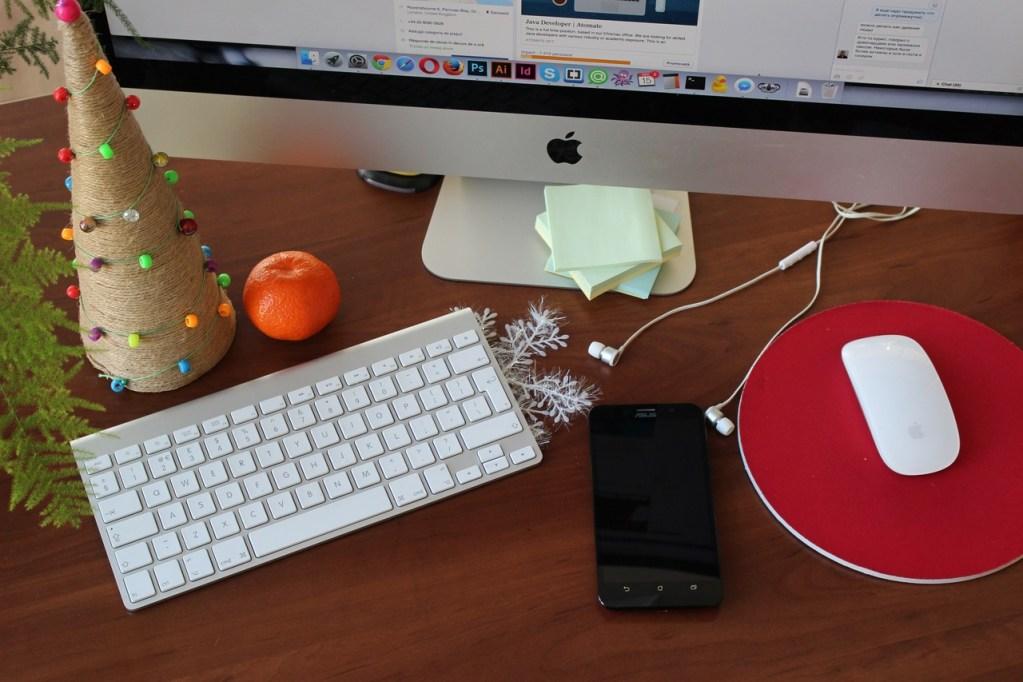 escritorio para computadora acompañado de adornos navideños, para ilustrar artículo sobre tips de marketing en facebook para la época navideña