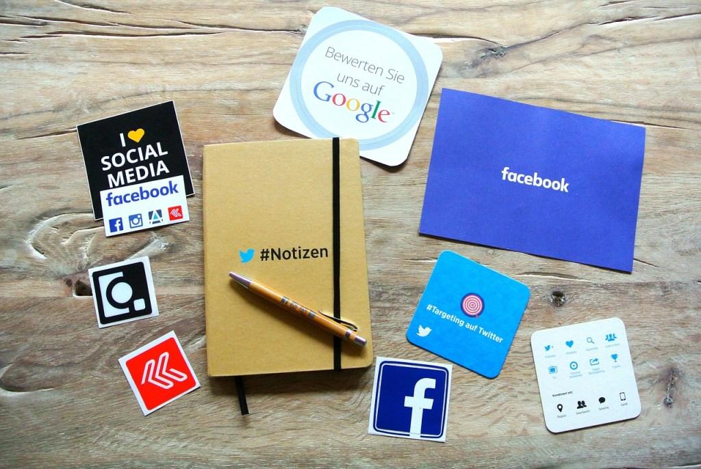 imagen ilustrativa para artículo sobre tendencias de marketing en redes sociales para 2017, donde se aprecian logotipos de diferentes redes sociales en papeles, stickers, agendas y demás